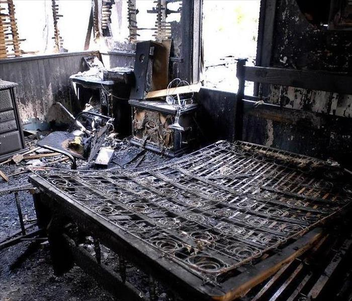 A bedroom is covered in soot and burnt after a fire