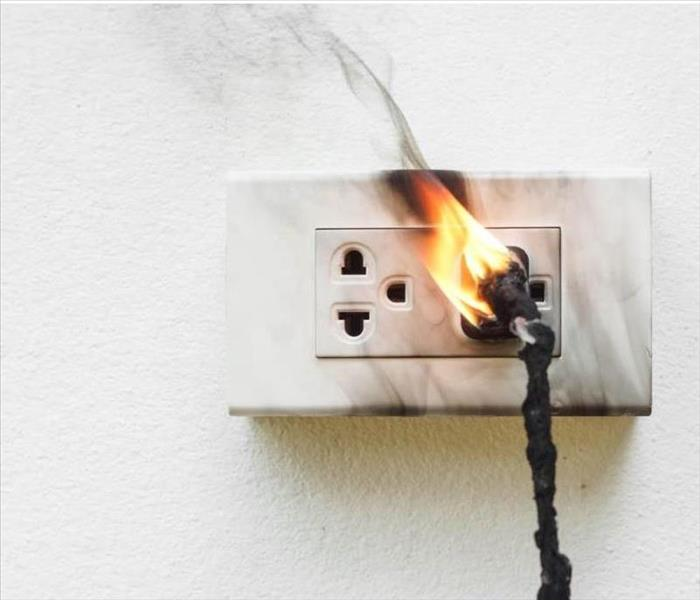 An electrical outlet catches fire due to a faulty wire