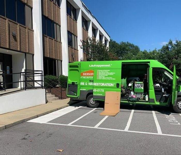 A green SERVPRO truck is parked in front of a three story office building